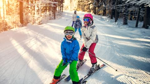 Family having fun skiing together on winter day