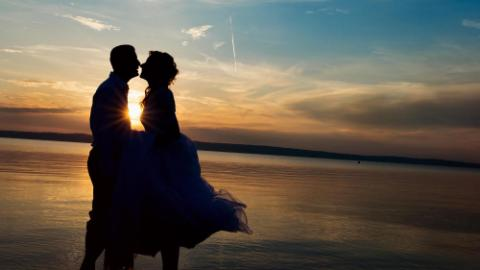 young wedding couple standing on the beach