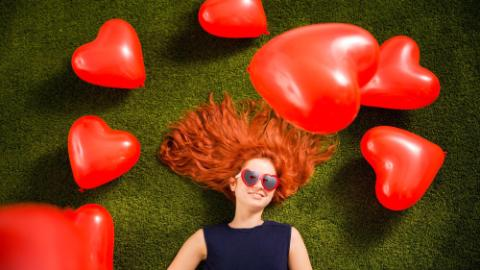 Young red head woman with heart shaped balloons