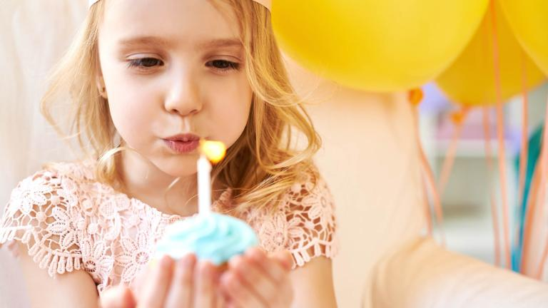 little girl blowing out candle on cupcake