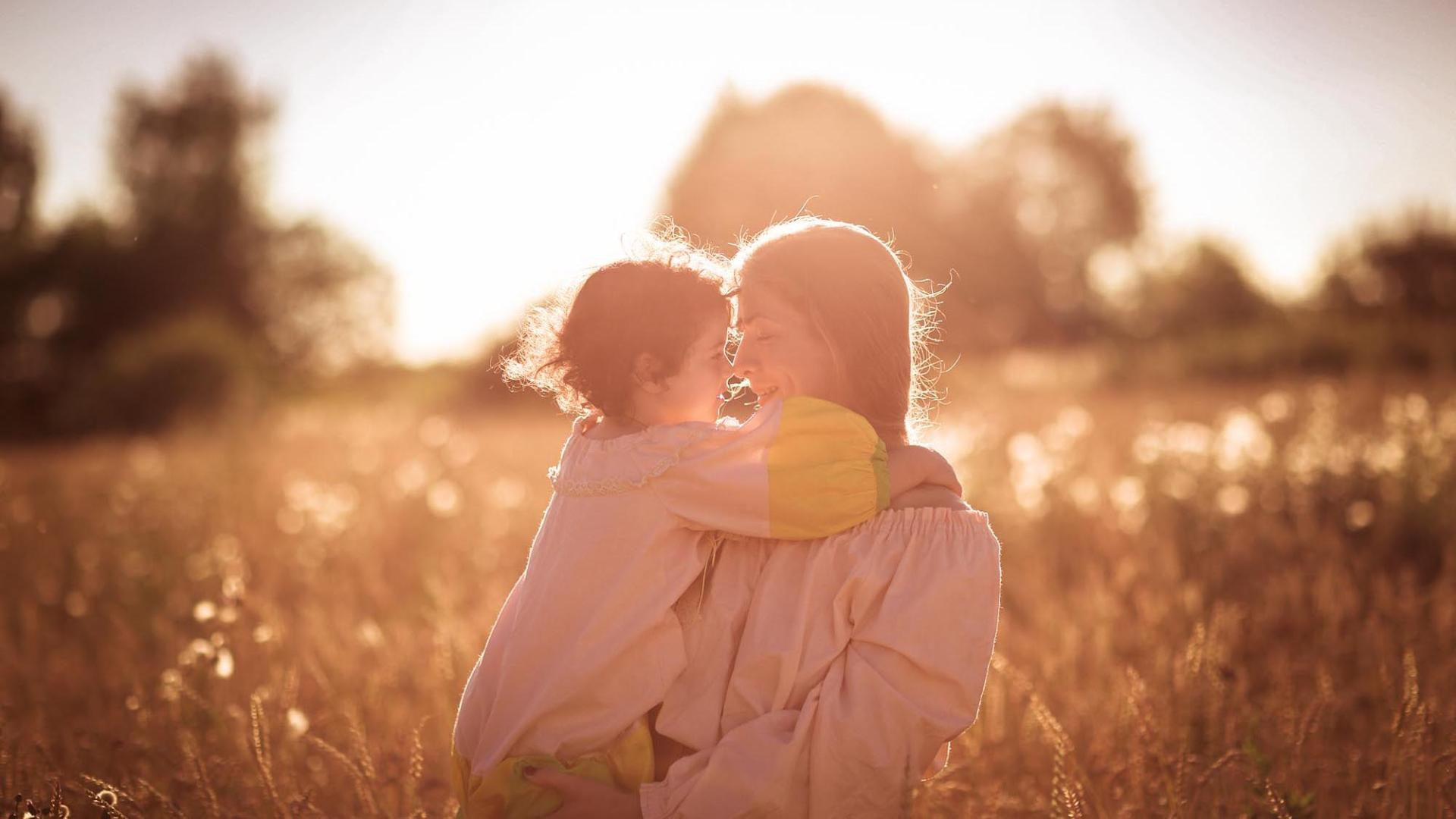 mother with daughter on the hands in a wheat field, On the Sunset embrace