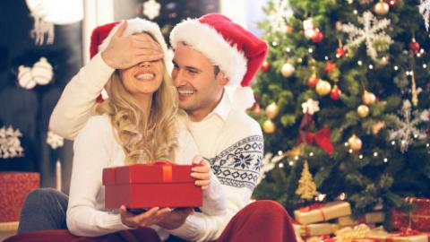 Young man and woman in Santa`s hat with Christmas present
