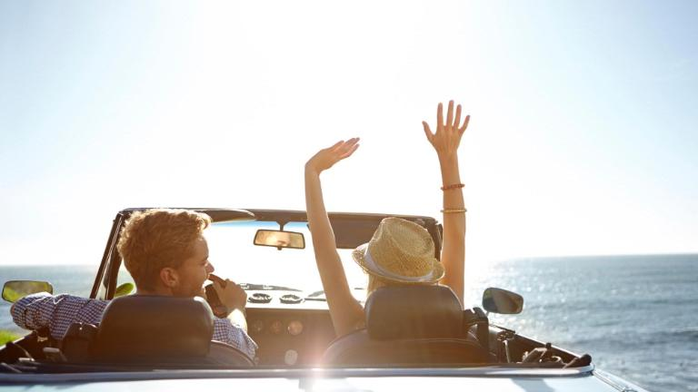 young couple parked by the ocean in a convertible on a sunny day