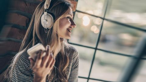 Happy woman listening music on headphones by the window